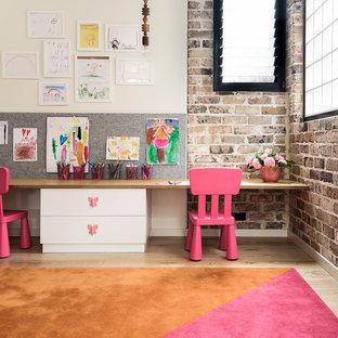 Foto di una cameretta per bambini da 4 a 10 anni industriale con parquet chiaro e pareti multicolore