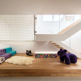 Свежая идея для дизайна: большая нейтральная детская с игровой в стиле модернизм с белыми стенами, паркетным полом среднего тона и коричневым полом для ребенка от 1 до 3 лет - отличное фото интерьера