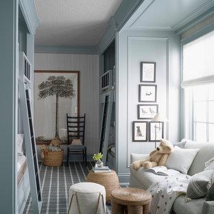 Foto på ett lantligt könsneutralt barnrum kombinerat med sovrum, med blå väggar, heltäckningsmatta och grått golv