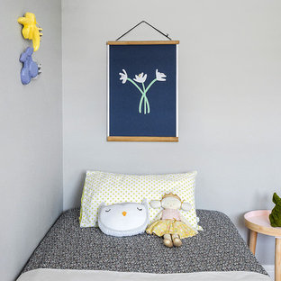 This is an example of a large contemporary kids' room for girls and kids 4-10 years old in Townsville with grey walls and light hardwood floors.