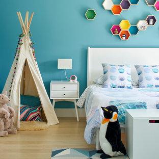 Foto på ett stort funkis könsneutralt barnrum kombinerat med sovrum och för 4-10-åringar, med blå väggar och ljust trägolv