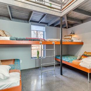 На фото: нейтральная детская в современном стиле с спальным местом, серыми стенами, бетонным полом и серым полом с