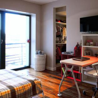 Bild på ett litet funkis flickrum kombinerat med skrivbord och för 4-10-åringar, med mellanmörkt trägolv, grå väggar och rött golv
