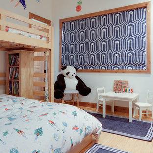 Eklektisk inredning av ett mellanstort pojkrum kombinerat med sovrum och för 4-10-åringar, med vita väggar och bambugolv