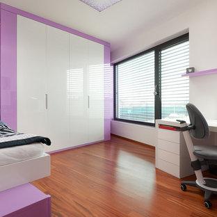 Exempel på ett mellanstort modernt barnrum kombinerat med skrivbord, med vita väggar och plywoodgolv