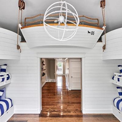 Inspiration for a coastal gender-neutral medium tone wood floor kids' room remodel in Nashville with white walls
