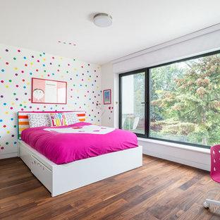 Ejemplo de dormitorio infantil de 4 a 10 años, minimalista, con paredes multicolor, suelo marrón y suelo de madera en tonos medios