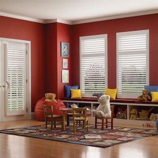 Immagine di una grande cameretta per bambini da 1 a 3 anni classica con pareti rosse, parquet chiaro e pavimento marrone