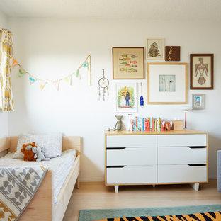 Immagine di una cameretta per bambini da 1 a 3 anni moderna con pareti bianche, parquet chiaro e pavimento beige