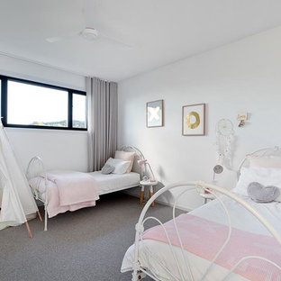 Design ideas for a beach style kids' bedroom for kids 4-10 years old and girls in Gold Coast - Tweed with white walls, carpet and grey floor.