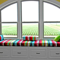 "Kids and Teens - Customer Photo |  ""Overlooking our field of corn, our School Room Window Seat with built in shelves needed something more. A custom cushion from Cushion Source finished it off beautifully!!! Thank you for the wonderful customer service, quick shipping of swatches so we could be sure we liked the colors, excellent follow-up, and speedy delivery. Our school room is now complete! This window seat cushion features Tropical Paint Stripe fabric with two pillows made in Tropical Paint Stripe."""