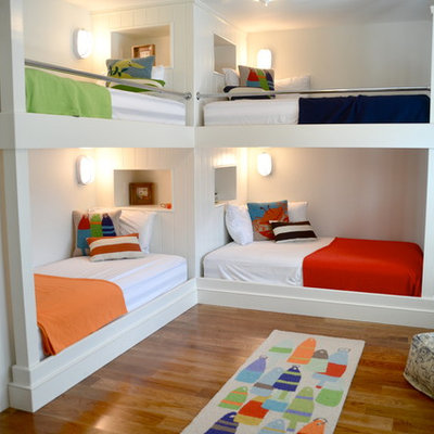 Example of a beach style gender-neutral medium tone wood floor kids' room design in Boston with white walls