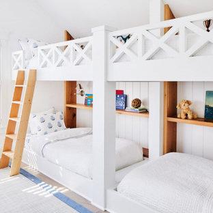 Maritim inredning av ett mellanstort könsneutralt barnrum kombinerat med sovrum och för 4-10-åringar, med vita väggar, mellanmörkt trägolv och brunt golv