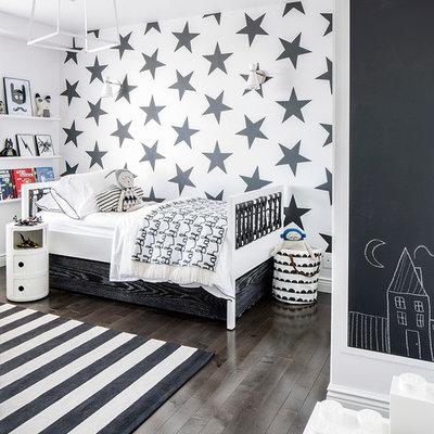 Example of a trendy dark wood floor and brown floor kids' room design in New York with multicolored walls