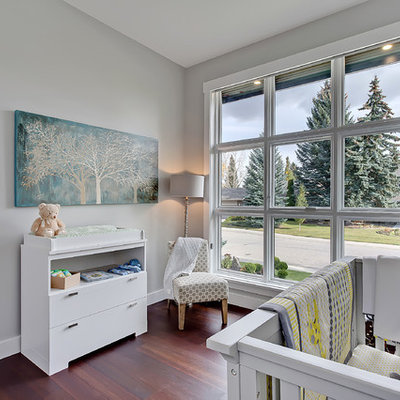 Mid-sized transitional gender-neutral medium tone wood floor kids' room photo in Calgary with gray walls
