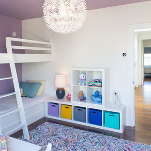 Contemporary toddler's room for girls in San Francisco with medium hardwood flooring and multi-coloured walls.