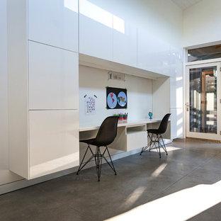 Inredning av ett modernt könsneutralt barnrum kombinerat med skrivbord och för 4-10-åringar, med vita väggar och betonggolv
