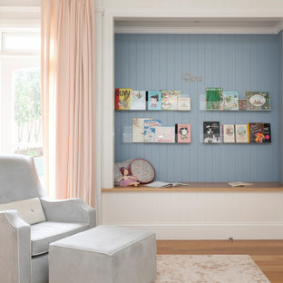 Design ideas for a large transitional kids' room for girls in Brisbane with blue walls, light hardwood floors, brown floor and panelled walls.