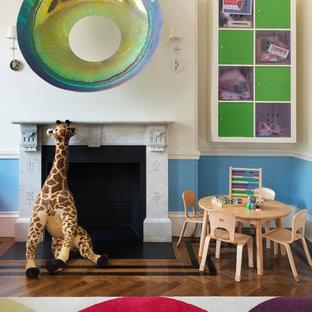 Immagine di una cameretta per bambini da 1 a 3 anni boho chic con pareti multicolore e pavimento in legno massello medio