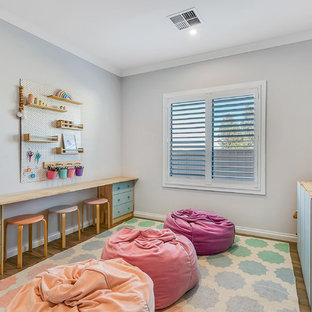 This is an example of a contemporary gender-neutral kids' playroom for kids 4-10 years old in Other with grey walls, medium hardwood floors and brown floor.