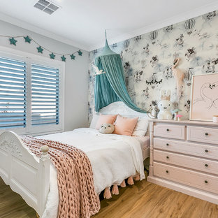 This is an example of a transitional kids' bedroom for kids 4-10 years old and girls in Other with grey walls, medium hardwood floors and brown floor.