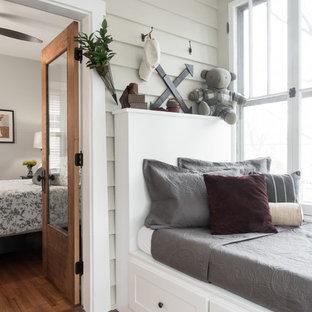 Immagine di una piccola cameretta per bambini da 4 a 10 anni boho chic con pavimento in legno massello medio e pareti beige