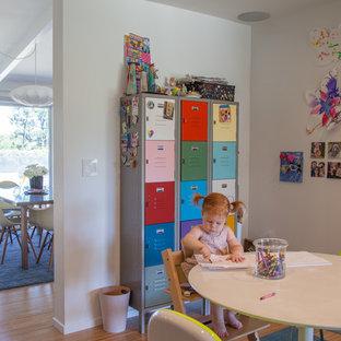 Exemple d'une chambre d'enfant de 1 à 3 ans rétro avec un mur blanc et un sol en bambou.