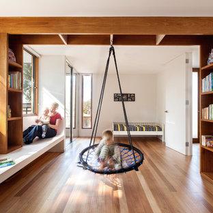 Idéer för stora funkis pojkrum kombinerat med sovrum, med mellanmörkt trägolv och vita väggar