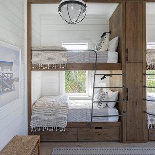 Idéer för att renovera ett stort maritimt könsneutralt barnrum kombinerat med sovrum och för 4-10-åringar, med vita väggar, mellanmörkt trägolv och beiget golv