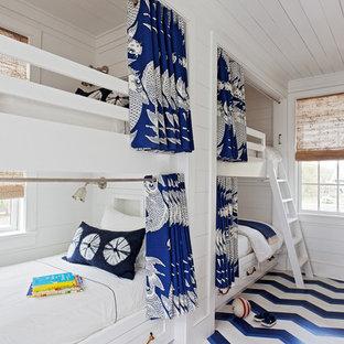 Cette image montre une chambre d'enfant marine avec un mur blanc, un sol en bois peint et un sol multicolore.