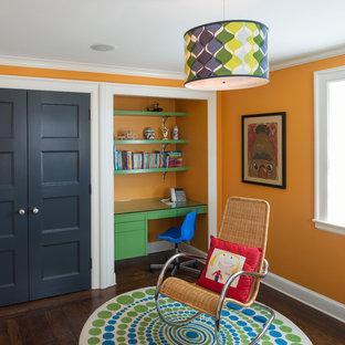 Cette photo montre une chambre de garçon tendance avec un sol en bois brun, un bureau et un mur orange.