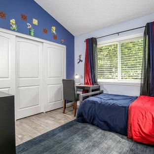 Ispirazione per una cameretta per bambini da 4 a 10 anni industriale con pareti blu, pavimento in laminato e pavimento grigio