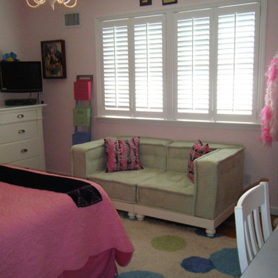 Inspiration for a mid-sized timeless girl medium tone wood floor kids' room remodel in New York with pink walls