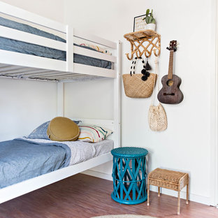 Inspiration for a beach style kids' bedroom in Wollongong with white walls, medium hardwood floors and brown floor.