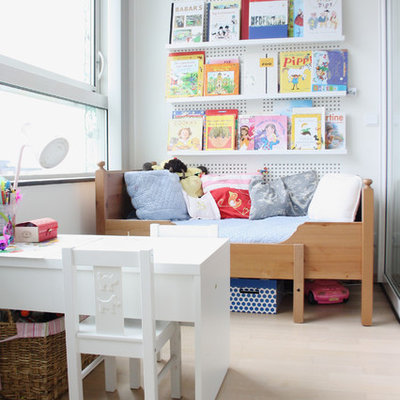 Kids' room - transitional gender-neutral light wood floor kids' room idea in Amsterdam with white walls