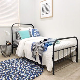 This is an example of a beach style gender-neutral kids' bedroom for kids 4-10 years old in Sydney with white walls, carpet and beige floor.