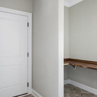 Cette image montre une grand chambre neutre de 4 à 10 ans rustique avec un bureau, un mur gris, un sol en brique et un sol beige.