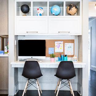 Immagine di una piccola cameretta per bambini da 4 a 10 anni classica con parquet scuro e pareti grigie