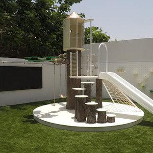 Inspiration pour une très grand chambre d'enfant de 4 à 10 ans design avec un mur blanc et un sol vert.
