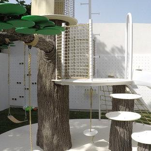 Esempio di un'ampia cameretta per bambini da 4 a 10 anni design con pareti bianche e pavimento verde