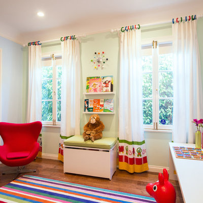 Example of a trendy girl medium tone wood floor playroom design in Los Angeles with green walls