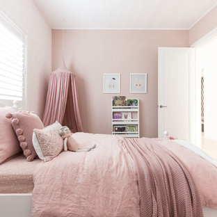 This is an example of a mid-sized traditional kids' room for kids 4-10 years old and girls in Sydney with pink walls, carpet and beige floor.