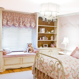 Inspiration for a timeless girl medium tone wood floor kids' bedroom remodel in Other with pink walls