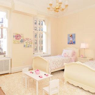 Ispirazione per una cameretta per bambini da 4 a 10 anni tradizionale con pareti beige e pavimento in legno massello medio