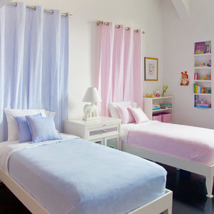 Example of a mid-sized classic gender-neutral dark wood floor kids' room design in New York with white walls