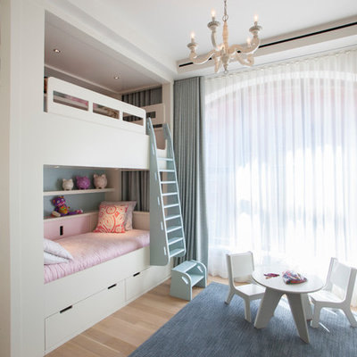 Kids' room - mid-sized transitional girl light wood floor kids' room idea in New York with white walls