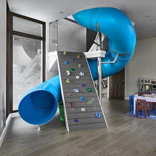Foto på ett stort funkis könsneutralt barnrum kombinerat med lekrum och för 4-10-åringar, med grå väggar, mörkt trägolv och grått golv