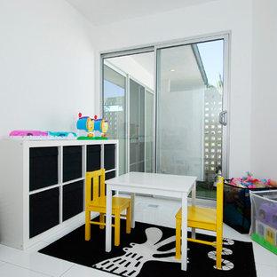 Inredning av ett modernt mellanstort könsneutralt barnrum kombinerat med lekrum, med vita väggar, linoleumgolv och vitt golv