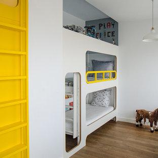 Immagine di una cameretta per bambini da 4 a 10 anni minimal di medie dimensioni con pareti bianche e pavimento in legno massello medio