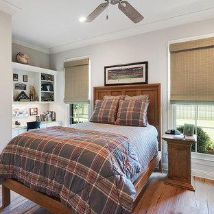 Ispirazione per una cameretta per bambini stile americano con pareti grigie, pavimento in legno massello medio e pavimento marrone